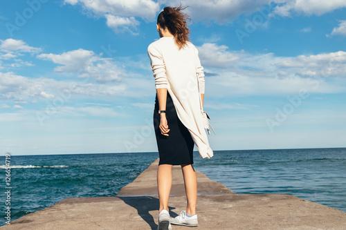 Fotografía  Slim brunette woman in a skirt, cardigan and sneakers walking on