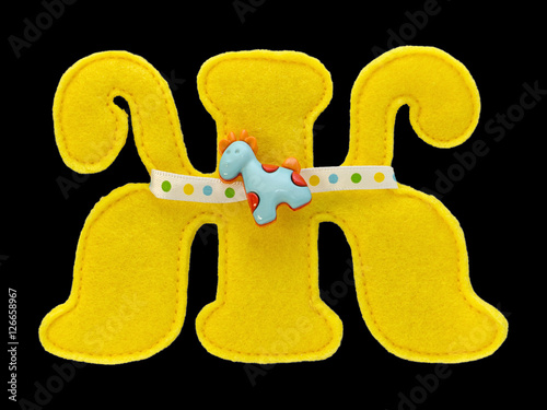 Fotografie, Obraz  Letter of the alphabet made of yellow felt isolated on black background