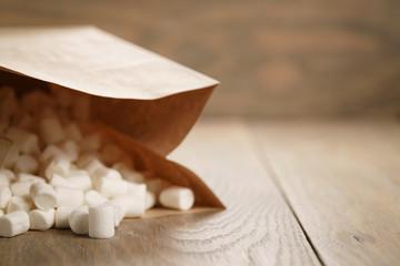 Fototapeta na wymiar marshmallow in brown craft paper bag on wooden table