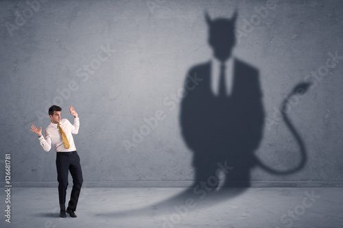 Foto  Business man looking at his own devil demon shadow concept