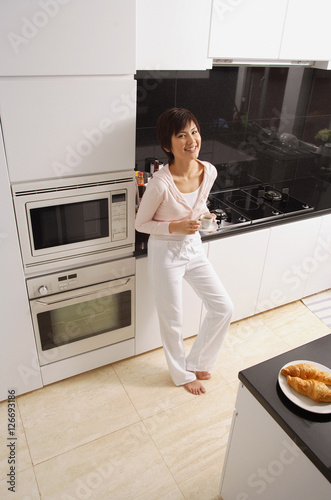 Young woman standing in kitchen, looking at camera, smiling