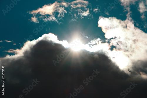 Fotografie, Obraz  Die Sonne scheint durch eine dicke Regenwolke über den geteilten Himmel