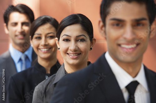 businessman in foreground, three colleagues in background, all smiling and looki Canvas Print