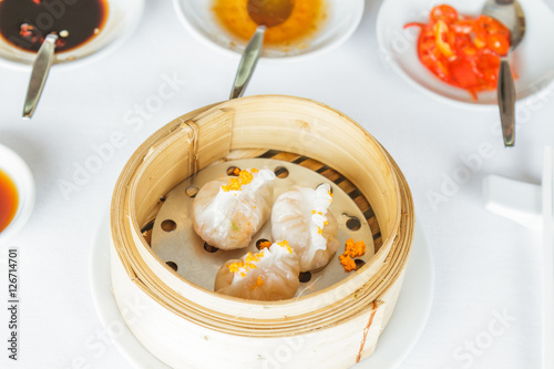 Photo  Dim sum food Steamed shrimp Fun Goh dumpling in bamboo basket at restaurant with soy sauce, sweet sauce, chili sauce and chopsticks