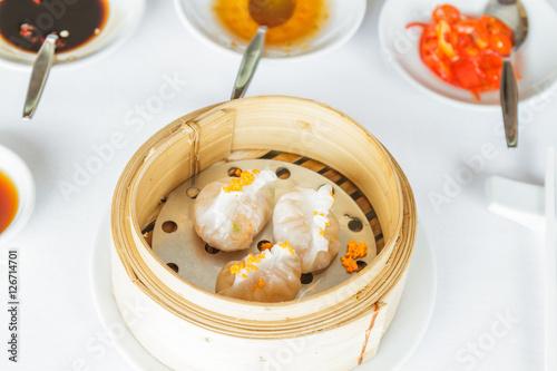 Dim sum food Steamed shrimp Fun Goh dumpling in bamboo basket at restaurant with soy sauce, sweet sauce, chili sauce and chopsticks Wallpaper Mural