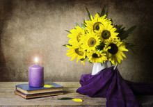 A Classic Still Life With Beautiful Sunflowers Placed In White Jar Which Wrapped In Purple Scarf And Candle On Vintage Books On Rustic Wooden Table..