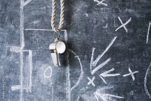 whistle of a soccer or football referee on black board with tact