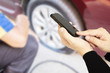 Man is using mobile phone to call someone over blurred technician is repairing car flat tire
