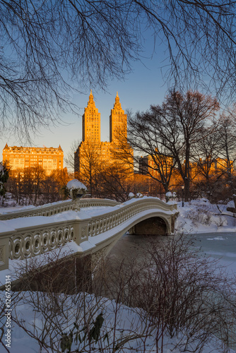 Central Park winter sunrise on the frozen Lake with  Bow Bridge and Upper West Side buildings. Manhattan, New York City