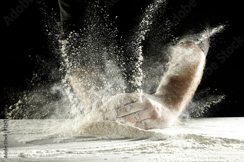 Fotografie, Obraz  hands and splash of flour with black background