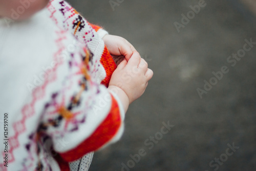 Caucasian toddler girl in white decorative poncho sweater
