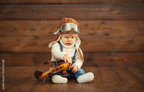 Plakat  funny baby boy pilot aviator with airplane laughing