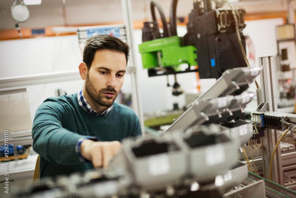 Fototapeta Mechanical engineer working on machines