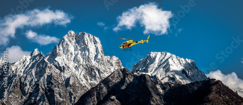 Tuinposter Helicopter Elicottero in volo tra le montagne
