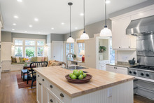 Amazing Luxury Kitchen Interior In White With Wooden Floor And Kitchen Island.