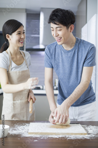 Happy young couple cooking in kitchen Poster