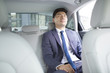 Confident businessman sitting in car back seat