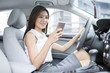 Confident businesswoman holding smart phone in a car