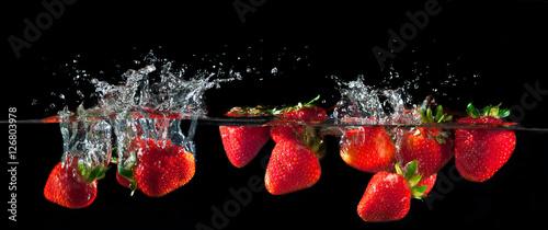 Strawberries splashing into water