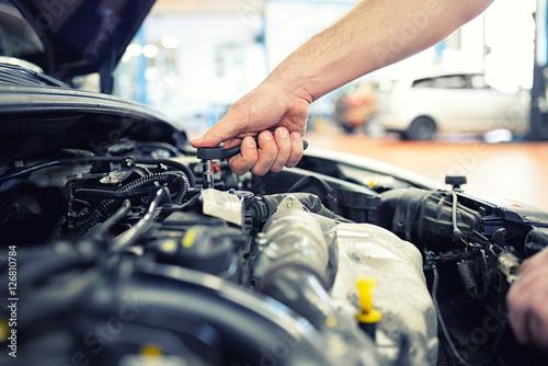 Zdjęcie XXL Mechanik samochodowy naprawy silnika pojazdu w warsztacie samochodowym - Zbliżenie dłoni z narzędziem w komorze silnika