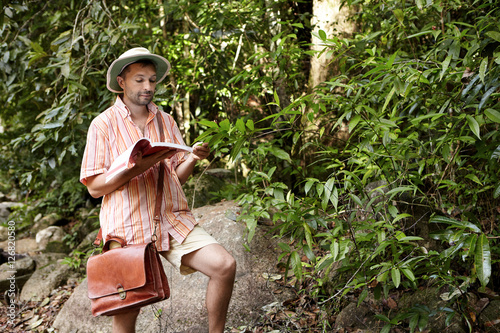 Fotografie, Obraz  Middle aged European biologist or ecologist wearing hat and briefcase reading no