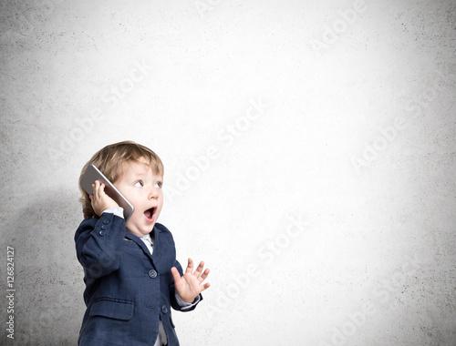 Obraz Cute little child on the phone near a concrete wall - fototapety do salonu