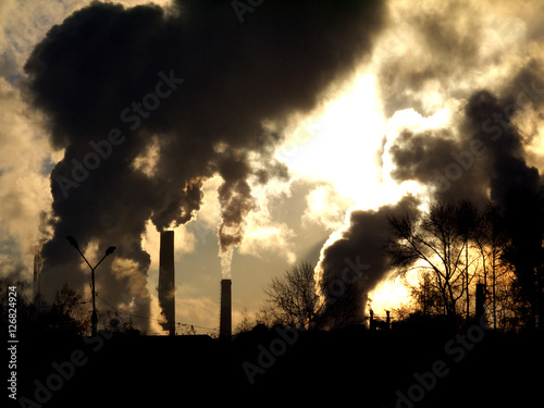 Fototapeta Smoking factory chimneys in morning backlighted by rising sun obraz na płótnie
