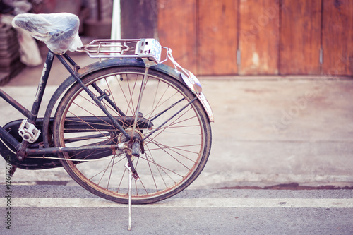 Montage in der Fensternische Fahrrad Old bicycle on wooden house wall background.