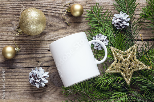 White coffee mug with gold Christmas decorations and fir branche