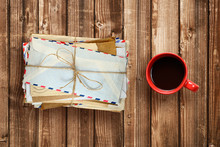 Pile Of Old Envelopes And Coffee Cup On Wooden Table Top View