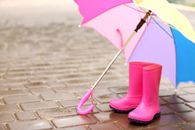 Colorful Umbrella And Gumboots On Wet Pavement