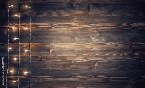 Fotomural Christmas lights on rustic wooden background.