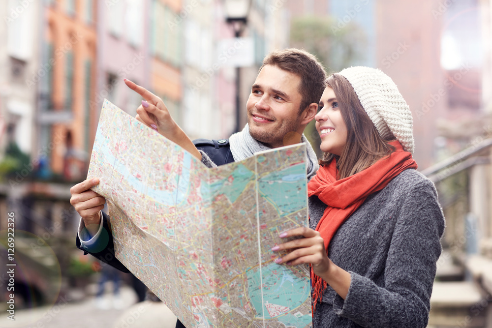 Fototapeta Pretty couple sightseeing with map