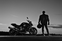 Silhouette Of Male Biker Stand...