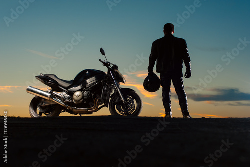 Silhouette of man in leather outfit with motorbike Billede på lærred