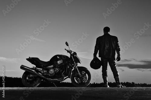 Silhouette of male biker standing next to bike Canvas-taulu