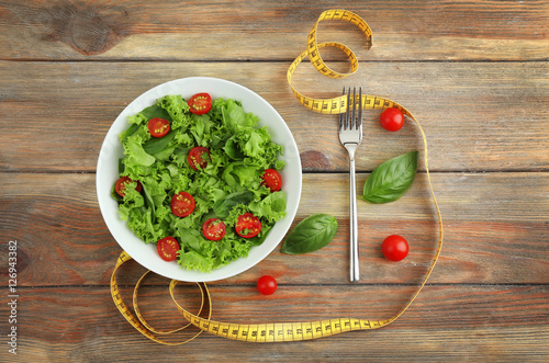 Photo  Fresh salad and measuring tape on wooden  background