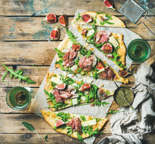 Fig, Prosciutto, Arugula And Sage Flatbread Pizza Cut Into Pieces With Glasses Of Rose Wine Over Rustic Wooden Background, Top View, Copy Space