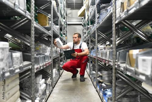Fotografie, Obraz  Mitarbeiter in einem Warenlager zwischen den Regalen