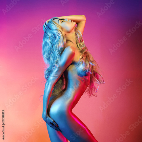Staande foto womenART Nude sexy blonde in colorful light.