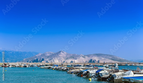Fotobehang Stad aan het water Wonderful romantic summer afternoon landscape panorama coastline Adriatic sea. Boats and yachts in harbor at cristal clear turquoise water. Baska on the island of Krk.