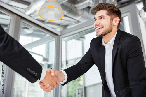 Fotografía  Two successful businessmen shaking hands on business meeting in office