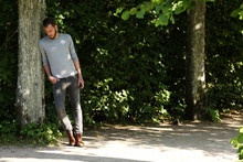 Man Leaning Back Against A Tree Wearing Jeans And A Grey Shirt, A Sunny Summer Day.