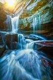 Tropical waterfall with sun rays