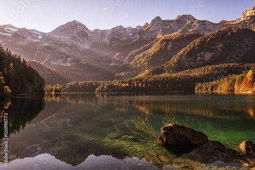 Foto auf Gartenposter Reflexion Mountain crystal clear lake with trees reflected in the water at sunset