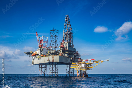 Staande foto Industrial geb. Offshore oil and gas drilling rig while completion well on oil and gas wellhead remote platform to running pipe line to oil and gas reservoir, Oil and gas production and exploration i.