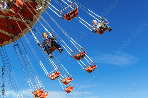 Poster Amusement Park Mother with the six-year-old son ride an attraction on a swing agains the blue sky in amusement park