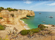 Algarve Portugal. Wild yellow rock cliffs and green-blue ocean