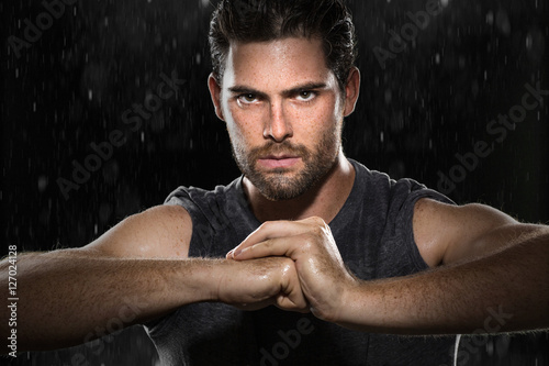MMA mixed martial arts fighter flexes strength conviction focused determination powerful glare rain