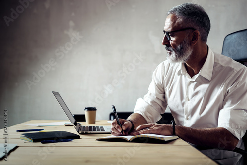 Fotografia  Adult stylish businessman wearing a classic glasses and working with laptop at the wood table in modern loft